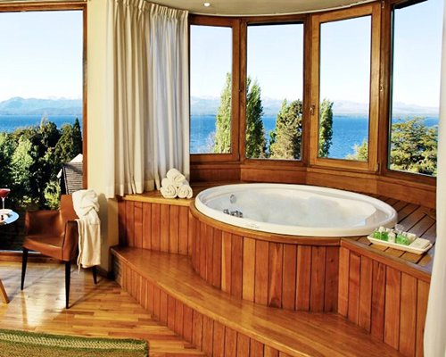 A wooden bathtub with an open lake view.