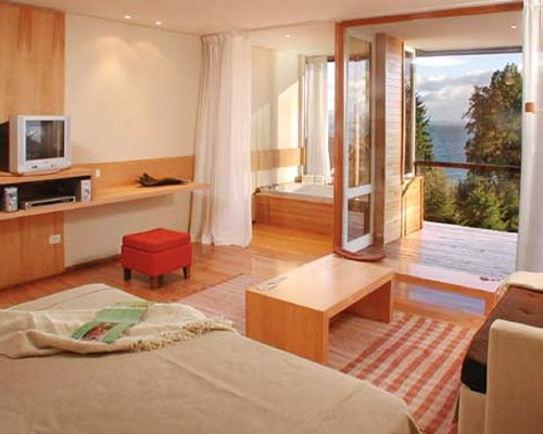 A well furnished bedroom with a television and a balcony.