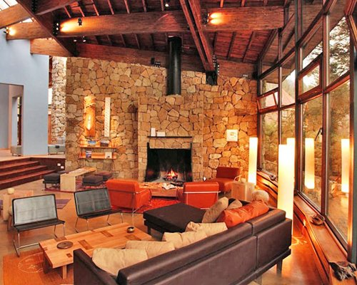 A well furnished living room with the fire in the fireplace.