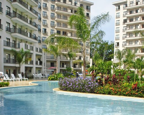 An outdoor pool with chaise lounge chairs and landscaping alongside the multi story condo.
