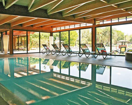 A large indoor swimming pool with chaise lounge chairs.