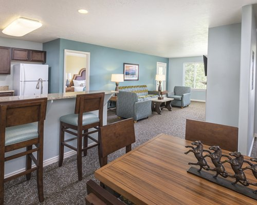 An open plan living dining and kitchen area with a breakfast bar television and outside view.