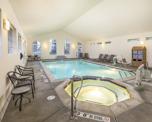 An indoor swimming pool with hot tub chaise lounge chairs and patio furniture.