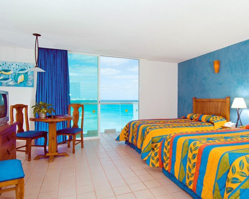 A well furnished bedroom with two beds television and a sea view.