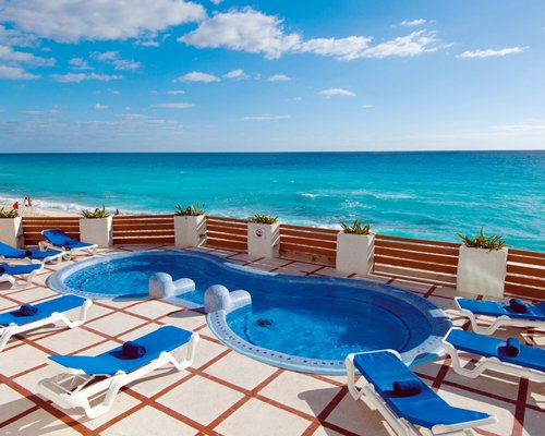 An outdoor kiddie pool with chaise lounge chairs alongside the sea.