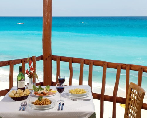 View of the beach and sea from a balcony with food items and beverages at the dining.