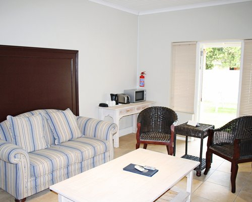 A well furnished living room with double pull out sofa microwave and coffee maker.