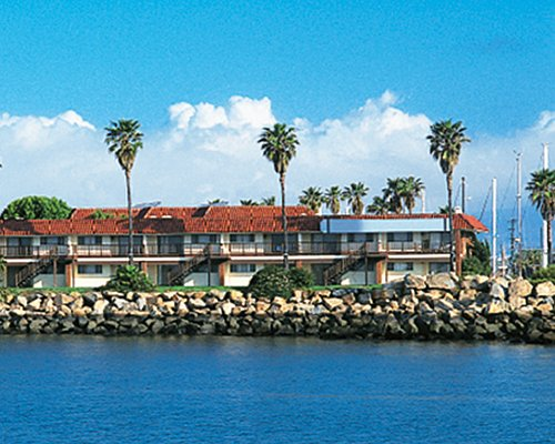 An exterior view of Vacation Internationale Oceanside Marina Inn resort alongside the waterfront.