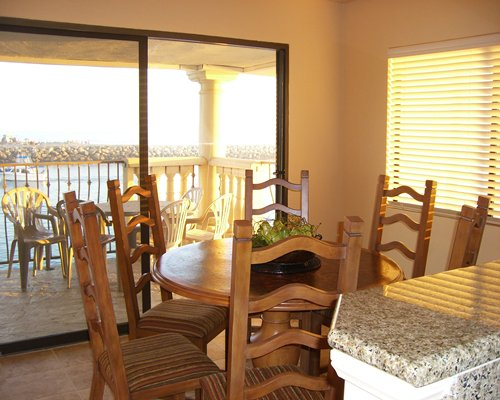 A well furnished dining area with a balcony and patio furniture.
