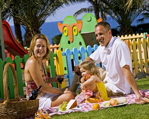 A family relaxing in an outdoor picnic area.