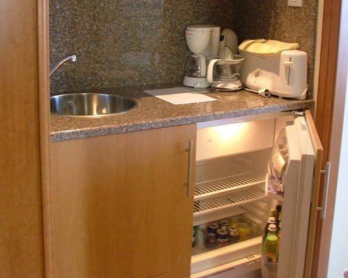 A kitchen with a mini refrigerator and an open sink.