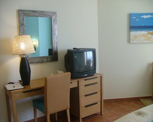 An indoor room with a dresser and a television.