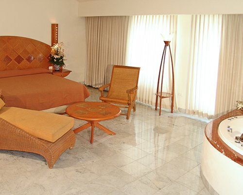 A well furnished bedroom with patio furniture chaise lounge chairs and bathtub.