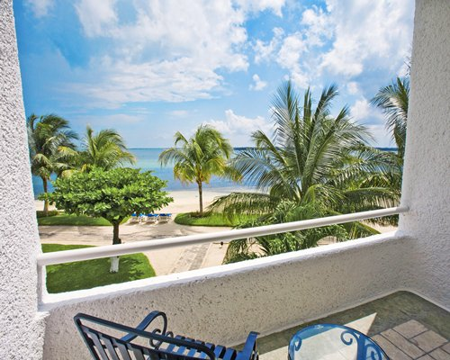 A scenic landscape and ocean from the balcony with patio furniture.