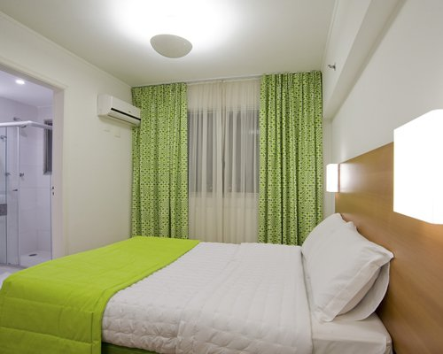 A well furnished bedroom alongside a stand up shower.