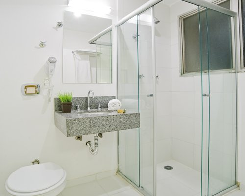 A bathroom with a sink and shower stall.