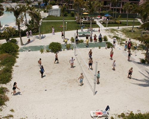 View of people playing in an outdoor volleyball court.