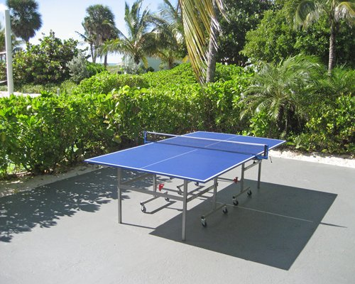 An outdoor recreational area with ping pong and landscaping.