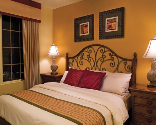 A well furnished bedroom with king bed and lamps.