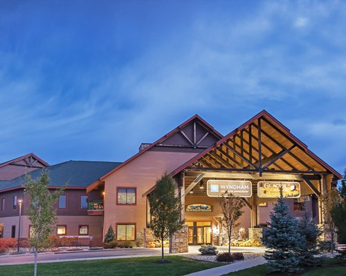 An exterior view of Wyndham Vacation Resorts At Glacier Canyon resort units at dusk.