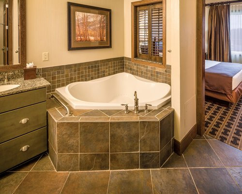 A bathroom with closed sink vanity bathtub and bedroom with a queen bed.