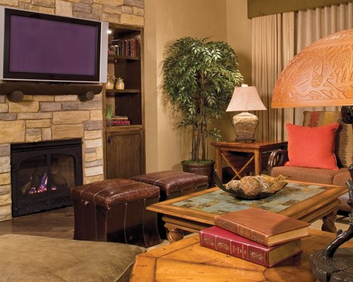 A well furnished living room with a television and fireplace.