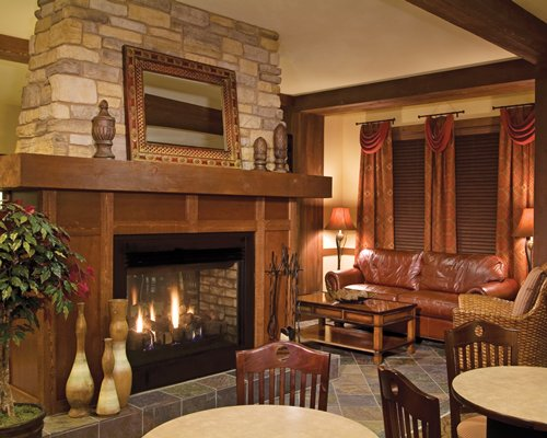 A well furnished living room with a fire in the fireplace and dining area.