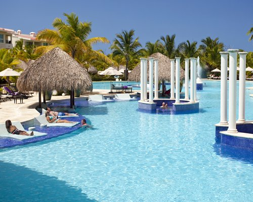 Large outdoor swimming pool with chaise lounge chairs thatched sunshades and palm trees.