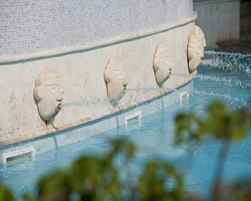 An outdoor swimming pool with water features.
