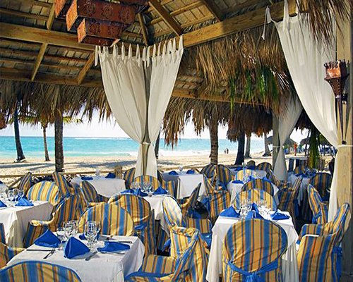 An outdoor fine dining area of the resort with the beach view.