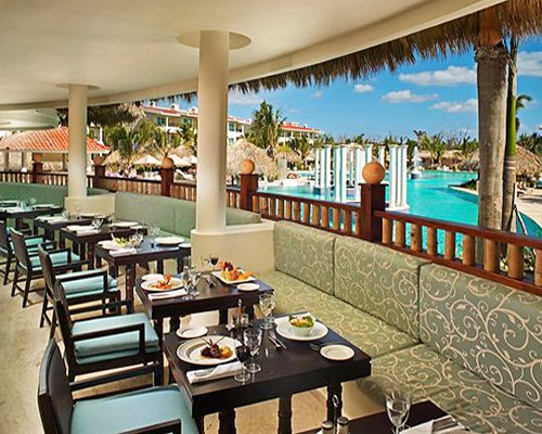 An indoor fine dining area at the resort alongside an outdoor swimming pool with thatched sunshades.