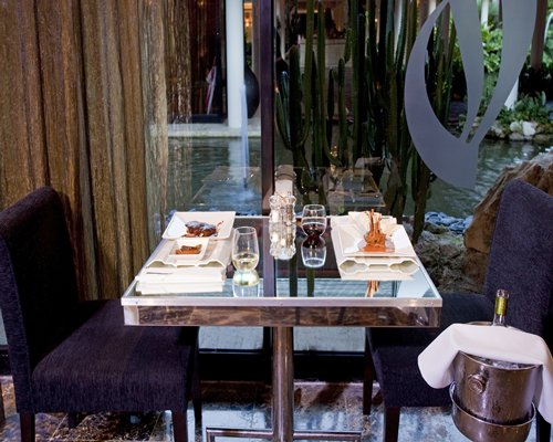 A well furnished glass topped dining table.