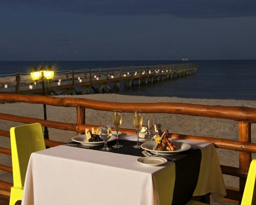 A wooden pier with dining area on the beach.