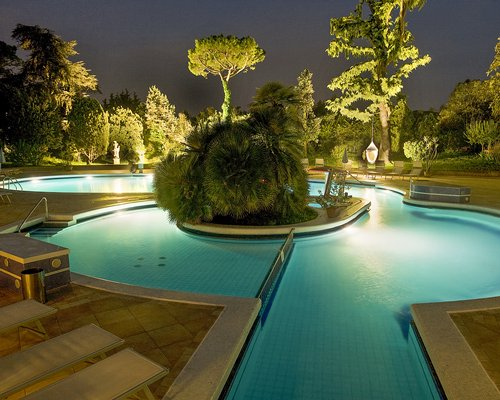 An outdoor swimming pool with chaise lounge chairs at night.
