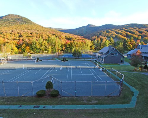 View of several outdoor tennis courts alongside multi story resort units.