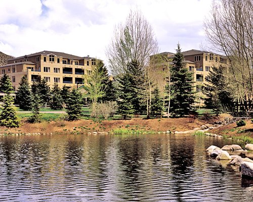 An exterior view of multi story resort units with the waterfront.