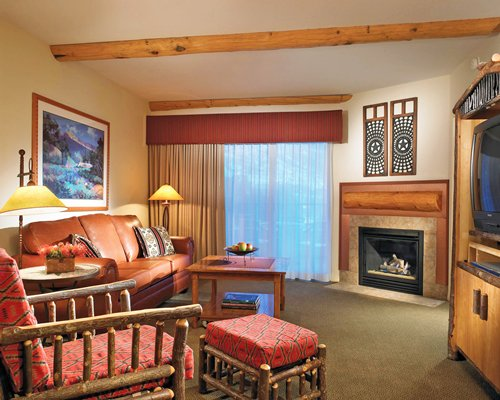 A well furnished living room with television and fireplace.
