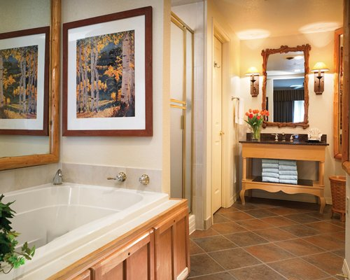 A bathroom with shower stall bathtub and open sink vanity.