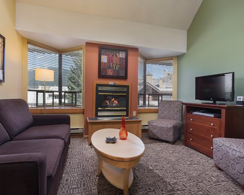 A well furnished living room with television fire in the fireplace and balcony.