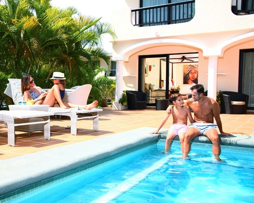 Family lounging around by exterior pool with view of room interior.
