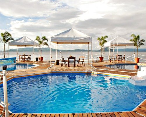 An outdoor swimming pool with patio furniture alongside the beach.