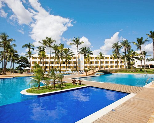 Exterior view of Pestana Sao Luis with an outdoor swimming pool wooden pathway bridge and palm trees.