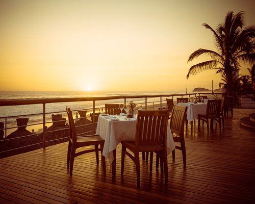 An outdoor fine dining restaurant with the view of the sunset.