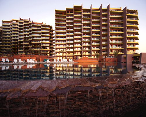 Exterior view of the resort with outdoor swimming pool and chaise lounge chairs at dusk.