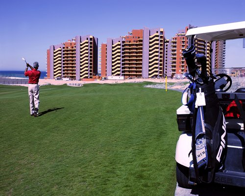 A man playing the golf course alongside the resort.
