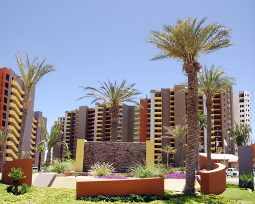 An exterior view of multi story resort units with trees.