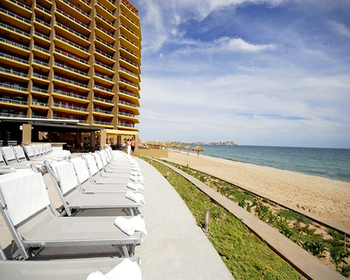 View of chaise lounge chairs alongside the multi story condo overlooking the beach.