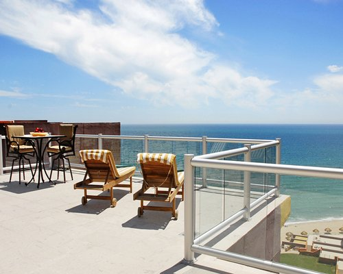 A balcony with chaise lounge chairs and patio furniture overlooking the beach.