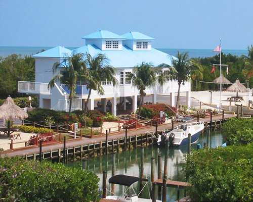 Exterior view of Ocean Pointe Suites @ Key Largo alongside the waterfront with boats.