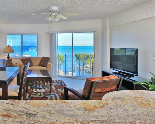 A well furnished living room with dining area television balcony and ocean view.